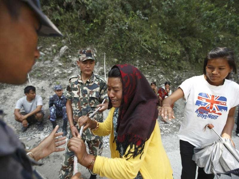 A woman, whose daughter is missing, cries near an area, swept away by a flash flood caused by an avalanche in the Annapurna mountain range on Saturday, in Kaski district. At least 19 people, including three foreigners, are confirmed to have died and 45 still missing till today due to the flood in Pokhara and adjoining villages in Kaski district, according to local media. (Reuters)