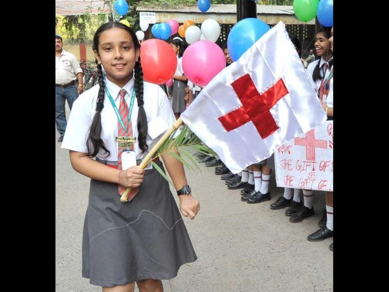 A girl holding a flag at Kargil Crossing in Patna during celebratiion of World Red Cross Day. Agencies