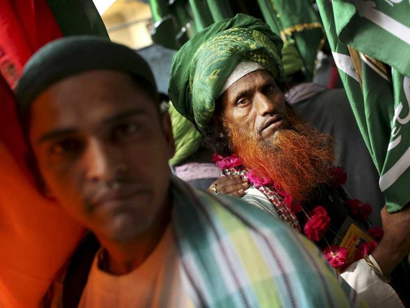 Sufi devotees who are on a pilgrimage to Ajmer Sharif, a revered Muslim shrine in Rajasthan, hold flags at a transit camp in New Delhi. (AP Photo/Kevin Frayer)