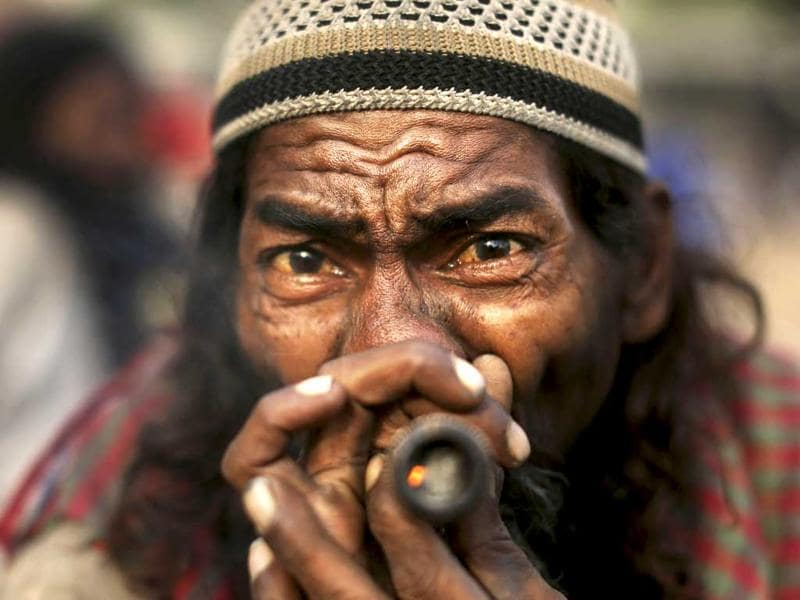 A Muslim Sufi devotee who is on a pilgrimage to Ajmer Sharif, in Rajasthan, smokes marijuana as he rests at a transit camp in New Delhi. (AP Photo/Kevin Frayer)