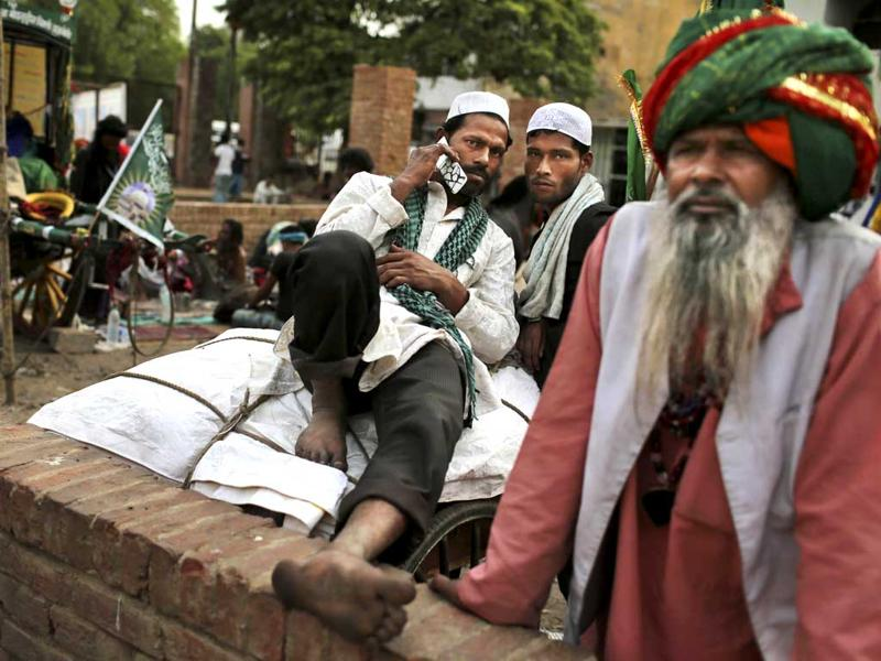 Sufi devotees who are on a pilgrimage to Ajmer Sharif, a revered Muslim shrine in Rajasthan, rest in New Delhi.(AP Photo/Kevin Frayer)