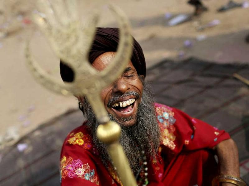 An Sufi devotee who is on a pilgrimage to Ajmer Sharif, a revered Muslim shrine in Rajasthan, laughs as he rests at a transit camp in New Delhi. (AP Photo/Kevin Frayer)