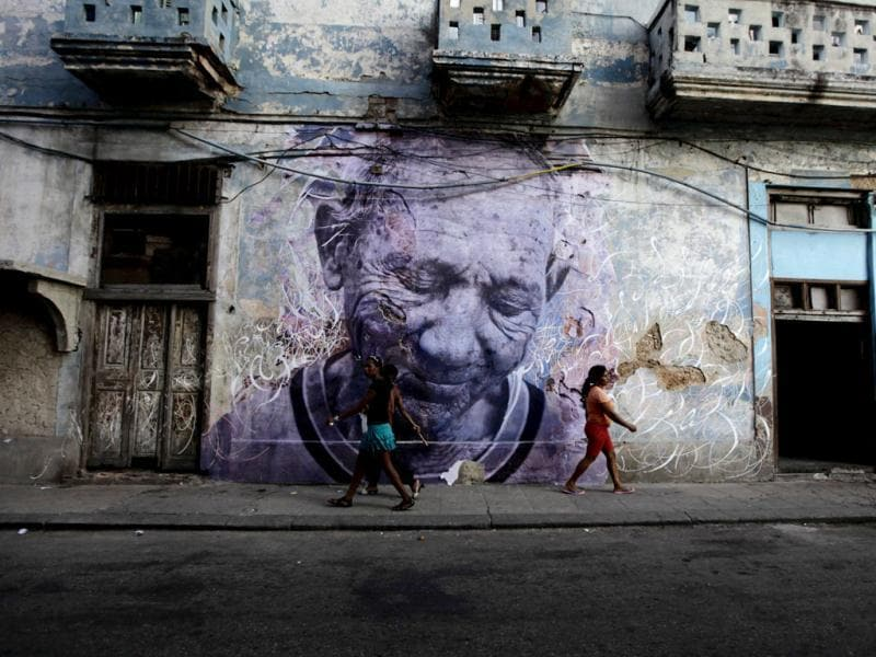 People walk beside a creation by Cuban-American artist Jose Parla and French artist J.R. on a street wall in Havana, which is part of the upcoming 11th Havana Biennial contemporary art exhibition. The project, titled Wrinkles Of The City, involves combining J.R's pictures of Cuban elderly people in the neighbourhood with Parla's calligraphic messages, and then pasting them on walls around the city. Reuters Photo/Desmond Boylan
