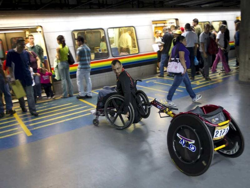 Miguel Ford, 37, a member of the Venezuelan Paralympics team, boards a subway car with his racing wheelchair after a practice session in Caracas. The roughly 40-person team is grateful to the socialist government of President Hugo Chavez - a highly controversial figure who has polarized Venezuela but is credited with pouring unprecedented resources into grassroots sports. Reuters/Carlos Garcia Rawlins