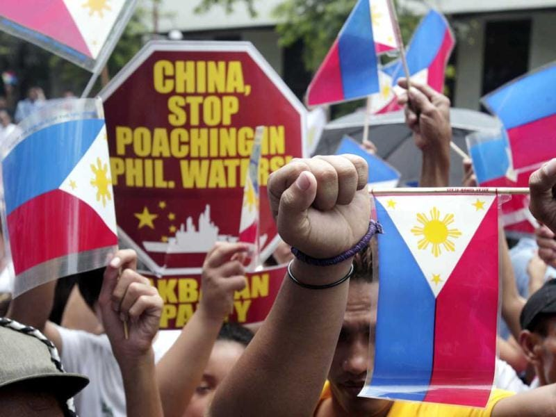 Protesters raise clenched fists during a rally in front of the Chinese consulate in Manila's financial district of Makati, Philippines. AP Photo/Pat Roque