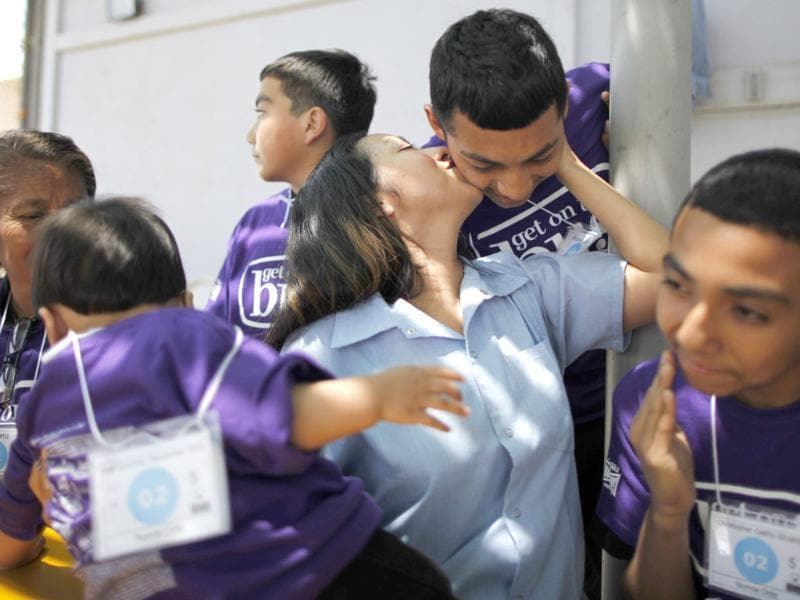 Norma Ortiz, 31, kisses one of her children as she sits next to her mother Olga Ortiz (L), 55. Norma's children are (L-R) 11-month-old Axel Ortiz, Jovanny Cedillo, Anthony Elizalde, and Christopher Cedillo. Norma has not seen Axel since he was born, and the other children for one and a half years. Reuters/Lucy Nicholson