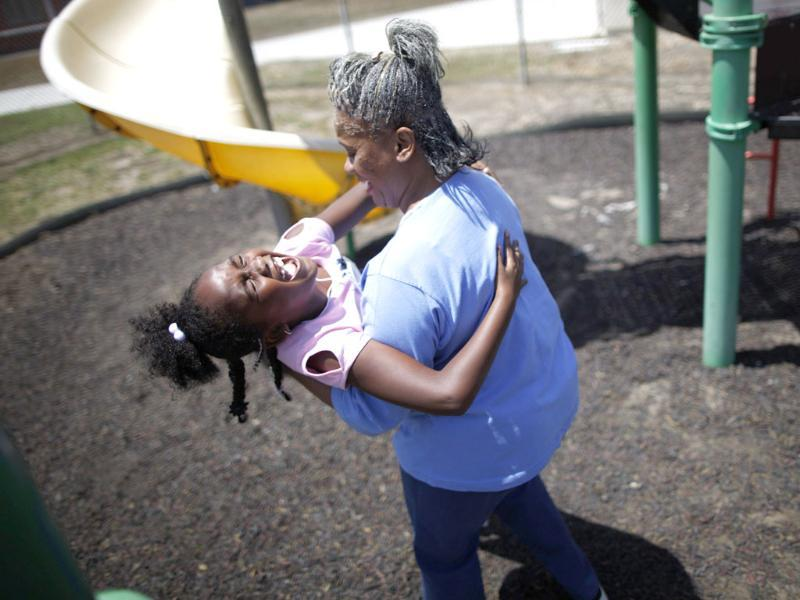 Fulorise Gadson (R) of Riverside plays with her daughter Ken'yida Draper, 7. 60% of parents in California Institute for Women state prison report being held over 100 miles from their children. Reuters/Lucy Nicholson