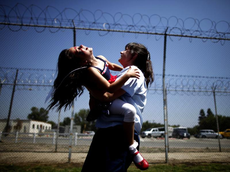 Cori Walters, 32, (R) hugs her daughter Hannah Walters, 6, at California Institute for Women state prison in Chino, California. An annual Mother's Day event, Get On The Bus, brings children in California to visit their mothers in prison. Reuters/Lucy Nicholson