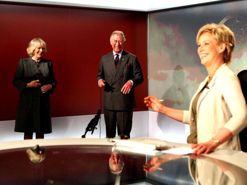 TV newsreader Sally Magnusson reacts as Britain's Prince Charles prepares to read the weather forecast with Duchess of Cornwall Camilla (L) in the Six O'Clock studio. AP Photo/Andrew Milligan, PA Wire
