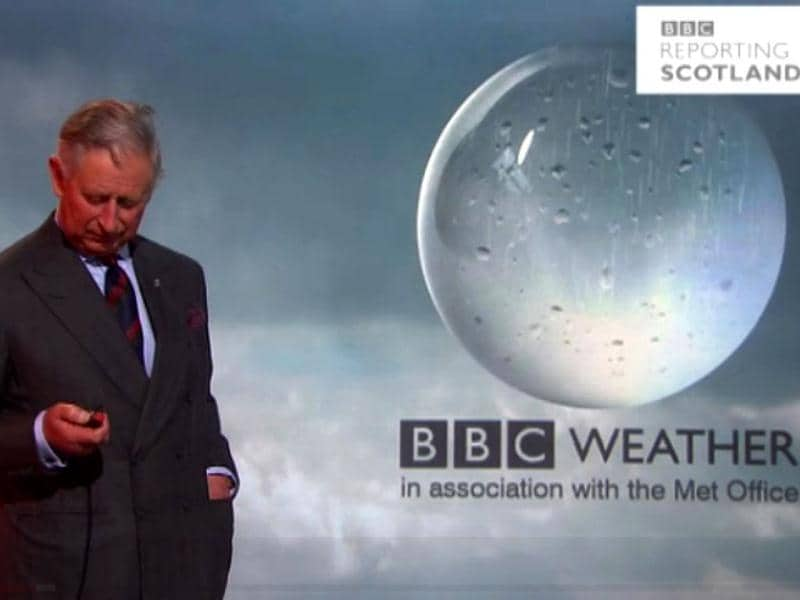 A handout image taken from footage courtesy of the BBC shows Britain's Prince Charles looking down at the button as he reads the weather forcast at the BBC studios in Glasgow. AFP Photo/Courtesy of the BBC