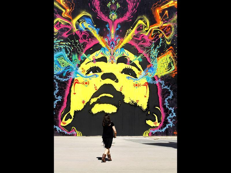 A woman walks past a graffiti art of Colombian artist Stinkfish at the Poliniza Festival of Urban Art at the Polytechnic University in Valencia. (Reuters/Heino Kalis)