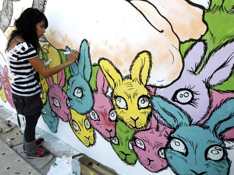 Mexican artist Dinora Palma puts the finishing touches to her graffiti art at the Poliniza Festival of Urban Art at the Polytechnic University in Valencia. (Reuters/Heino Kalis)