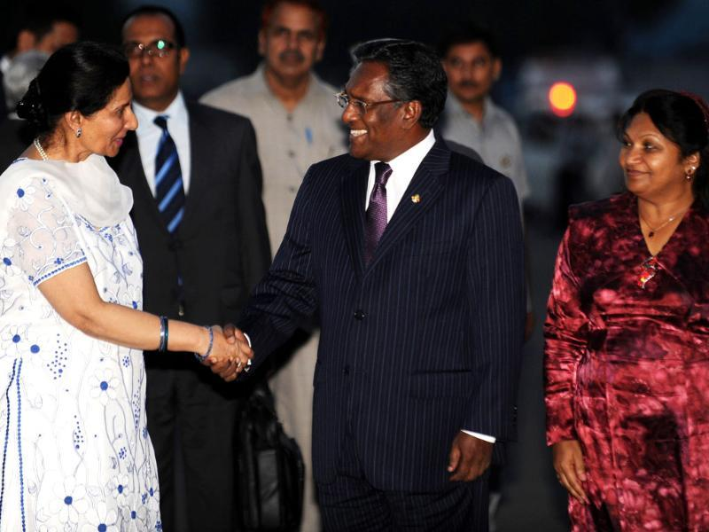 Minister of state for external affairs Preneet Kaur (L) shakes hands with Maldives president Mohamed Waheed Hassan (C) as his wife Ilham Hussain looks on during their arrival in New Delhi. AFP/Raveendran