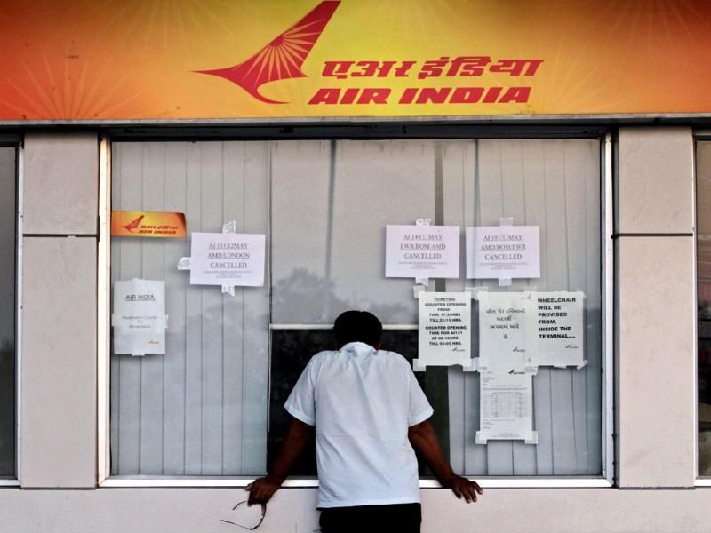 A passenger makes an enquiry at an Air India counter at the airport in Ahmedabad. Hundreds of passengers have been stranded after the airlines cancelled around 20 international flights due to a strike by pilots. AP/Ajit Solanki