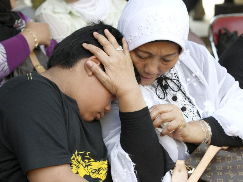 An Indonesian woman comforts his grandson whose father was on board of the Russian-made plane that crashed into a mountain in West Java, as they wait for the identification process of the victims at the main police hospital in Jakarta, Indonesia. AP/Dita Alangkara