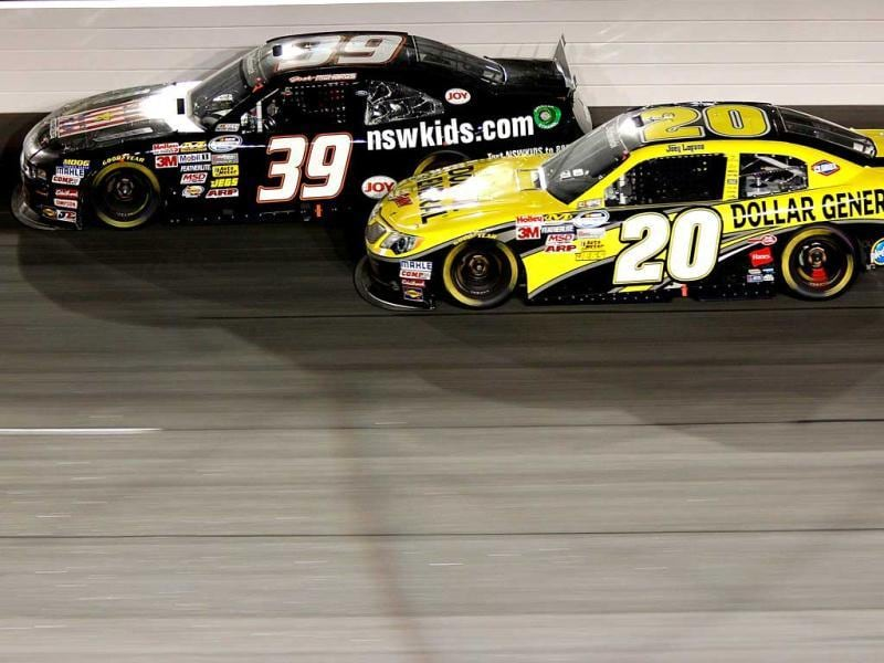 Josh Richards, driver of the #39 NSW Kids Ford, and Joey Logano, driver of the #20 Dollar General Toyota, race during the NASCAR Nationwide Series VFW Sport Clips Help A Hero 200 at Darlington Raceway on May 11, 2012 in Darlington, South Carolina. (AFP Photo)