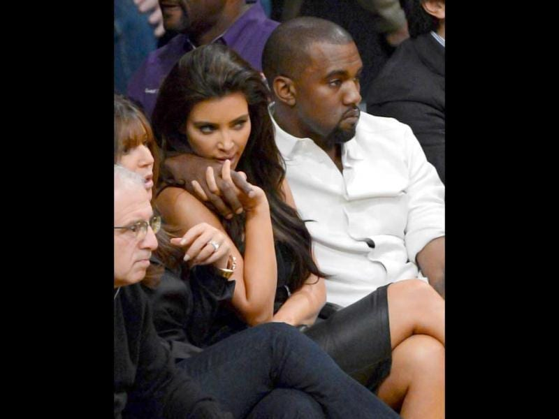 Kanye West puts his arm around Kim Kardashian from their courtside seats as the Los Angeles Lakers take on the Denver Nuggets in Game Seven of the Western Conference Quarterfinals in the 2012 NBA Playoffs at Staples Center in Los Angeles, California. AFP/Kevork Djansezian
