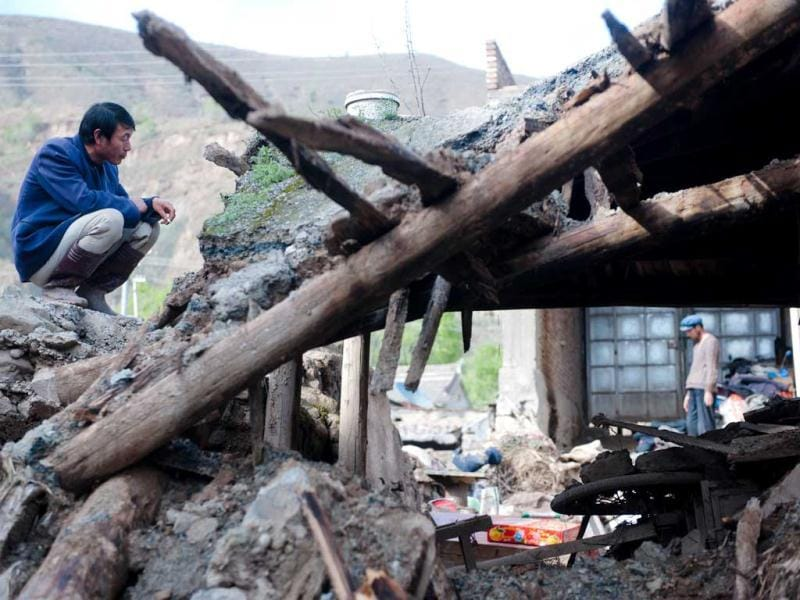 A man checking his damaged home after a storm hit the village in Minxian, north China's Gansu province. AFP Photo