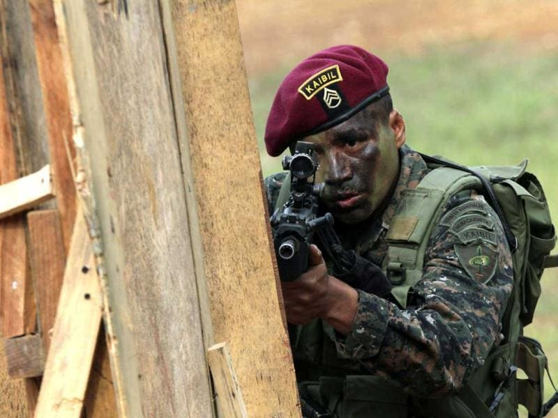 A member of the Kaibil, an elite group of the Guatemalan army, participates in an urban operation exercise in the jungle near their base in Poptum, Peten, 400 km (248 miles) from Guatemala City. The Kaibil was founded in 1974 and is currently involved in the fight against Mexican drug cartels, particularly against the Los Zetas, according to the spokesperson for the Ministry of Defense of Guatemala. (Reuters)