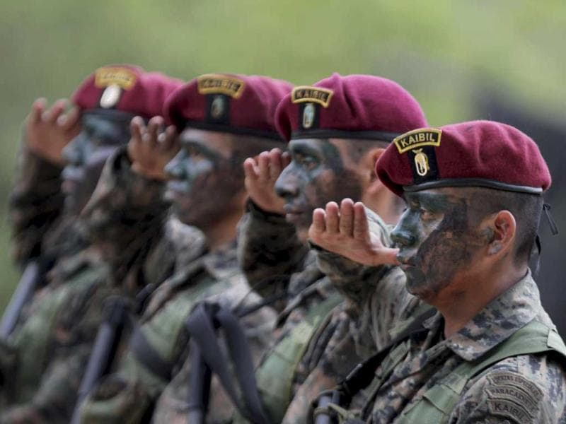 Kaibiles, members of an elite group of the Guatemalan army, salute as they stand in formation in the jungle near their base in Poptum, Peten, 400 km (248 miles) from Guatemala City. The Kaibil was founded in 1974 and is currently involved in the fight against Mexican drug cartels, particularly against the Los Zetas, according to the spokesperson for the Ministry of Defense of Guatemala. (Reuters)