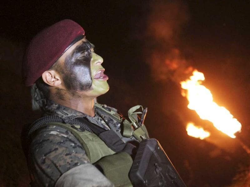 A member of the Kaibil, an elite group of the Guatemalan Army, sings during a welcoming ceremony in Cerro del Honor, Hill of Honor, in his base in Poptum, Peten, 400 km (248 miles) from Guatemala City. The Kaibil was founded in 1974 and is currently involved in the fight against Mexican drug cartels, particularly against the Los Zetas, according to the spokesperson for the Ministry of Defense of Guatemala. (Reuters)