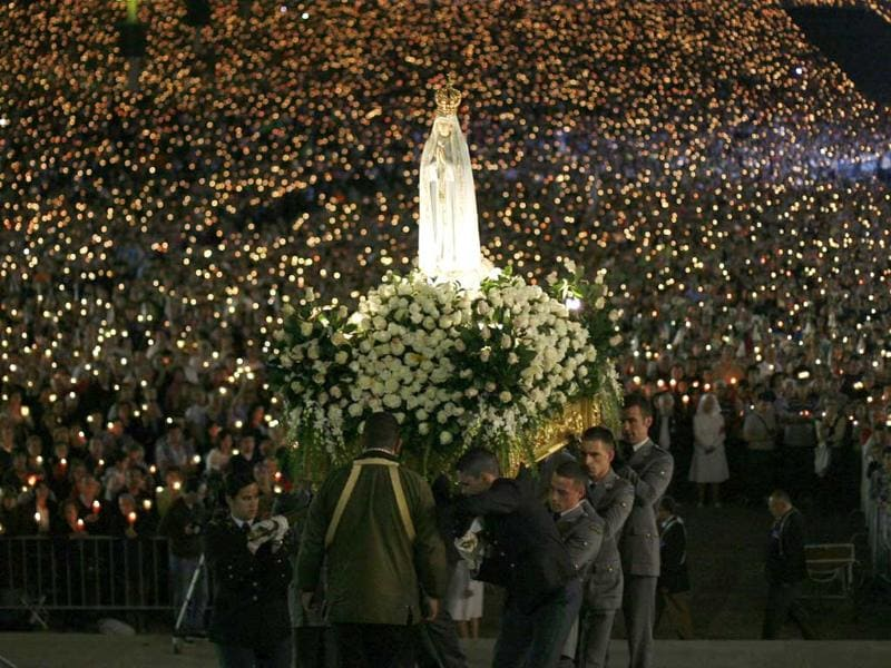 A statue of the Holy Virgin Mary of Fatima is carried during a candlelight vigil at the Fatima holy shrine in central Portugal. Thousands of pilgrims are on their way to the Fatima Shrine to attend the 95th anniversary celebrations of the first appearance of the Virgin Mary to three shepherd children in 1917. REUTERS/Rafael Marchante