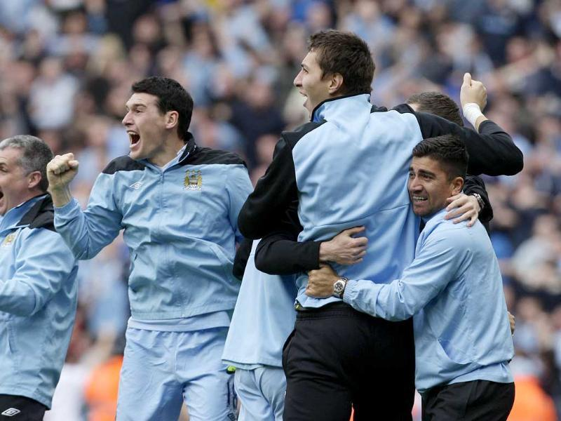 Manchester City's Gareth Barry, left, celebrates with team members after winning the English Premier League title after their soccer match against Queens Park Rangers at the Etihad Stadium, Manchester, England. AP/Jon Super