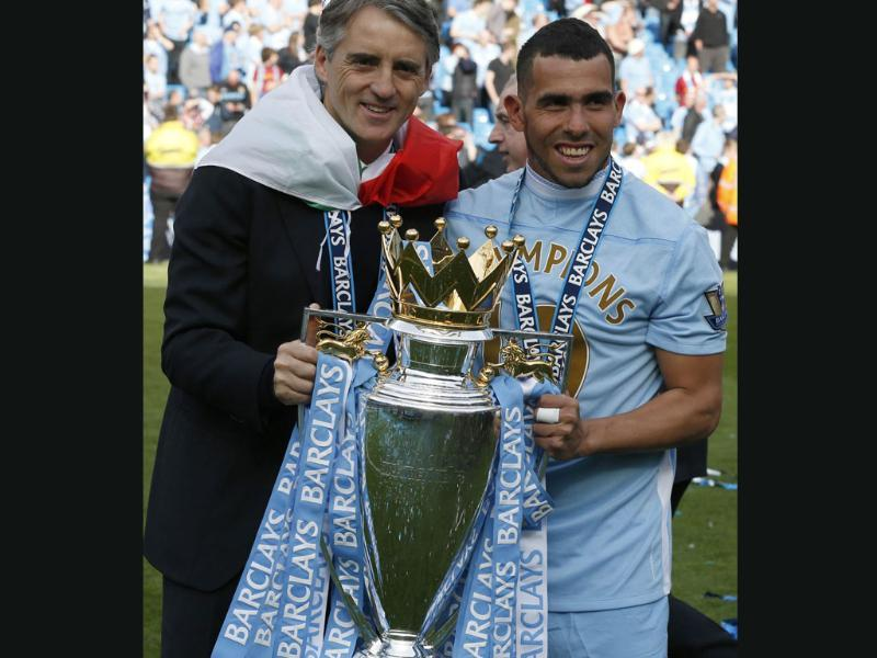 Manchester City's manager Roberto Mancini holds the English Premier League trophy with Carlos Tevez following their soccer match against Queens Park Rangers at the Etihad Stadium in Manchester, northern England. Reuters/Phil Noble