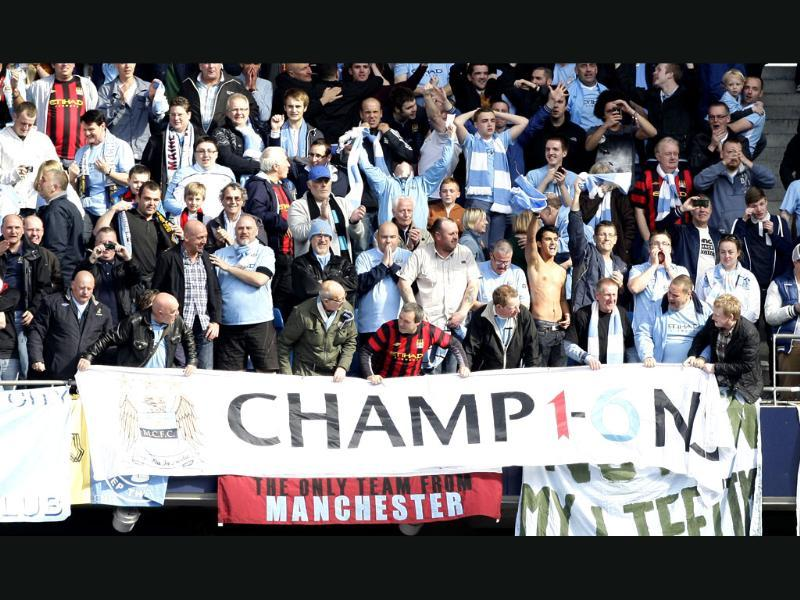 Manchester City fans celebrate after winning the English Premier League title after the match against Queens Park Rangers at the Etihad Stadium, Manchester, England. AP/Jon Super