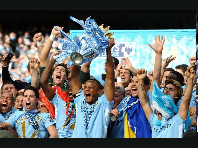 Manchester City's Belgian captain Vincent Kompany lifts the Premier league trophy after their 3-2 victory over Queens Park Rangers in the English Premier League football match at the Etihad stadium in Manchester. AFP/Paul Ellis