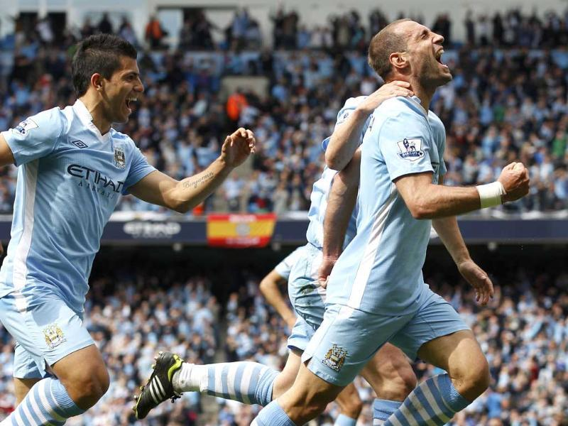 Manchester City's Pablo Zabaleta (R) and Sergio Aguero celebrate Zabaleta's goal during their English Premier League soccer match against Queens Park Rangers at the Etihad Stadium in Manchester, northern England. Reuters/Darren Staples