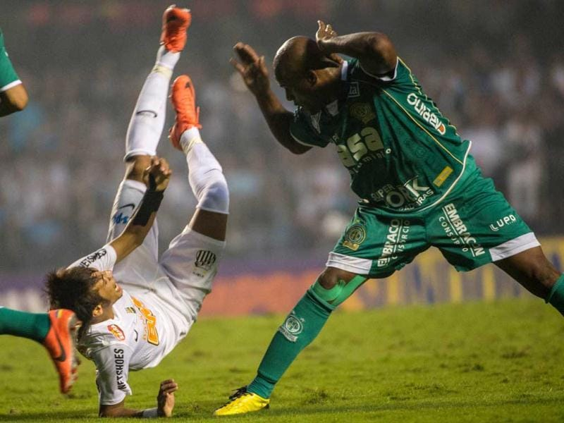 Santos's footballer Neymar (L) falls next to Guarani's Domingos during the final of the Paulista Championship -- the main football tournament of the state of Sao Paulo -- at Morumbi stadium in Sao Paulo, Brazil. Santos defeated Guarani 4-2 and won the championship for the third consecutive time. AFP/Yasuyoshi Chiba