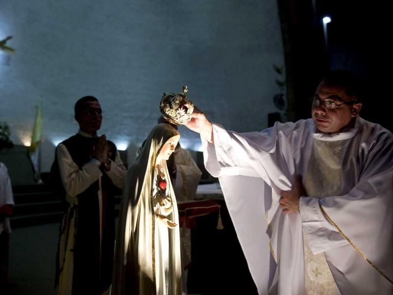 A priest places a crown on a statue of Our Lady of Fatima before a mass at the metropolitan cathedral in Managua, Nicaragua. (AP Photo/Esteban Felix)