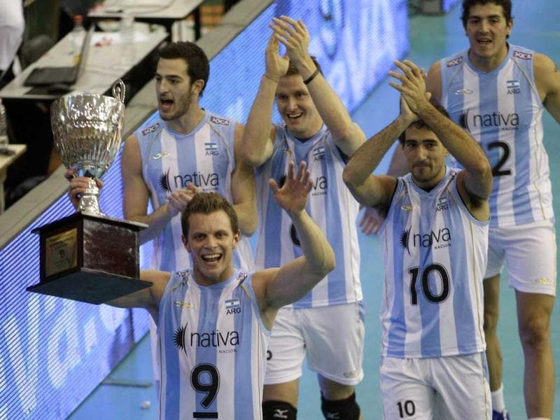 Argentina's Rodrigo Quiroga lifts the trophy after his team beat Venezuela during an Olympic volleyball qualifying match in Buenos Aires, Argentina. AP/Eduardo Di Baia