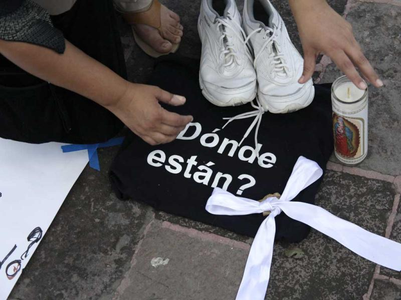 A woman arranges a pair of tennis shoes over a black bag during a protest for the killing of 49 people by hitmen in Cadereyta at the Macroplaza in Monterrey. The words on the bag read,
