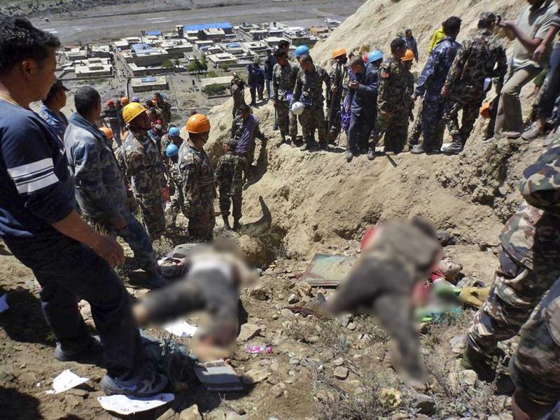 Bodies of victims lie on the ground as Nepalese rescue workers inspect the site of the crash near Jomsom airport, 200 kilometers northwest of the capital, Katmandu, Nepal. (AP Photo)