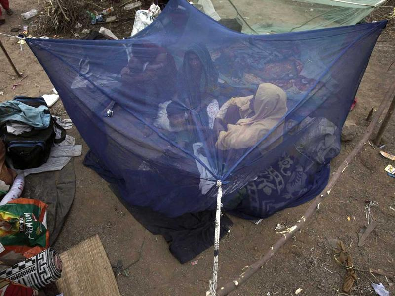 A family, who said they belonged to the Burmese Rohingya community from Myanmar, sit inside a mosquito net at a makeshift shelter at a camp in New Delhi. REUTERS/Adnan Abidi