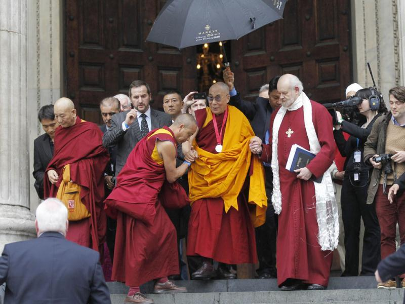 Dalai Lama, Tibetan Buddhist spiritual leader, center, leaves St. Paul's Cathedral in London after receiving the 2012 Templeton Prize awarded to him for encouraging scientific research and harmony among religions. AP Photo/Sang Tan