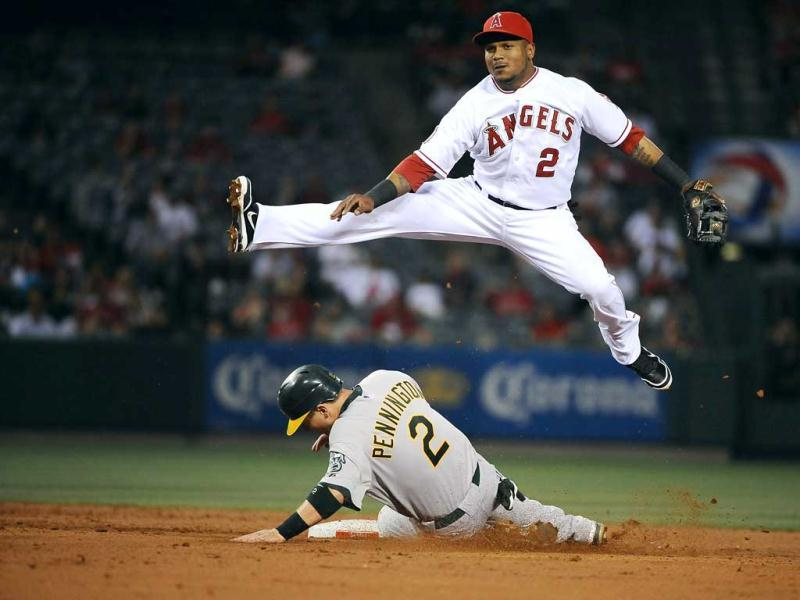 Erick Aybar #2 of the Angels of Anaheim turns a double play over Cliff Pennington #2 of the Oakland Athletics in the third inning at Angel Stadium of Anaheim in Anaheim, California. Jonathan Moore/AFP