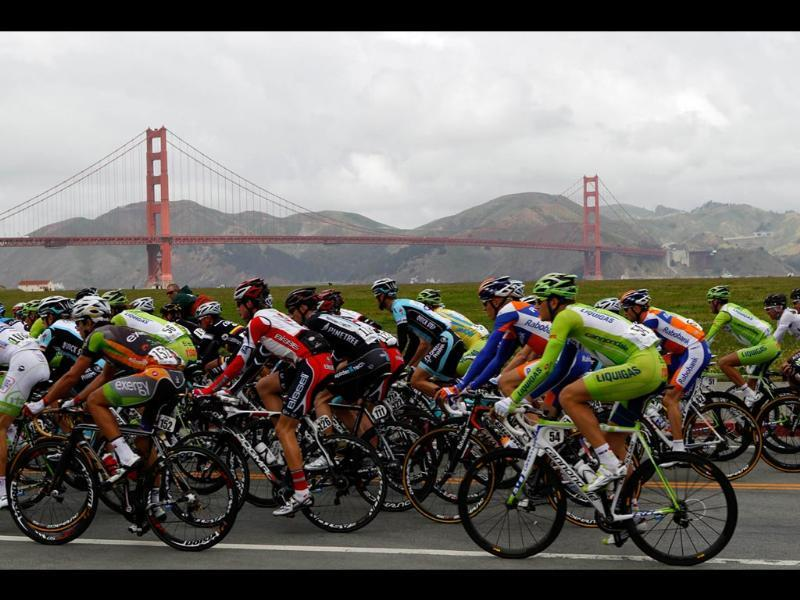 Riders cycle along Crissy Field and the Golden Gate Bridge during Stage 2 of the Tour of California cycling race in San Francisco, California. REUTERS/Robert Galbraith