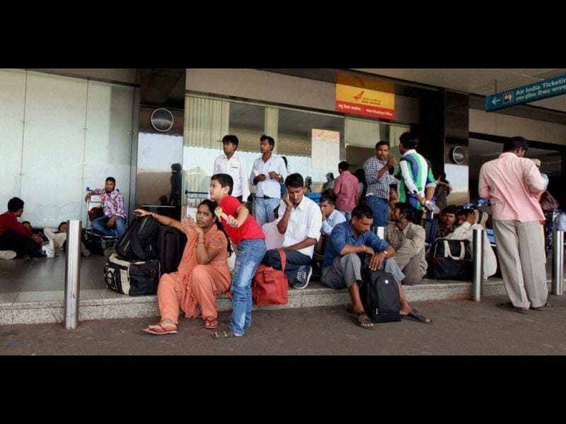 Passengers wait outside the booking office of Air India at the Mumbai International Airport following cancellation of several Air India flights. (PTI Photo)