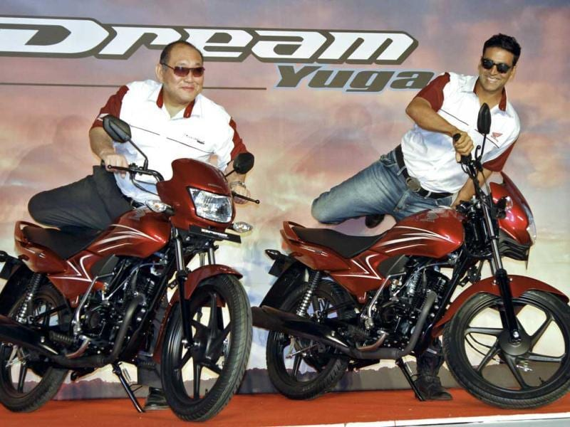 Keita Muramatsu, president of Honda's India unit, and Bollywood actor Akshay Kumar mount on newly launched 110cc Dream Yuga motorbikes in Gurgaon on the outskirts of New Delhi . Reuters/B Mathur