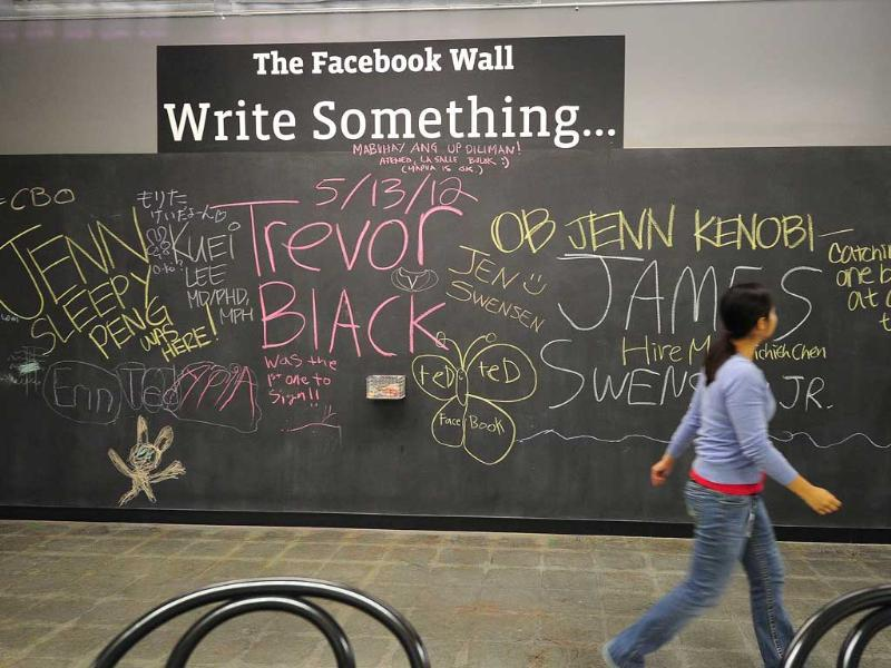 An employee walks past 'The Facebook Wall', a chalkboard on which employees can write or draw whatever they want, at the Facebook campus in Menlo Park. AFP/Robyn Beck