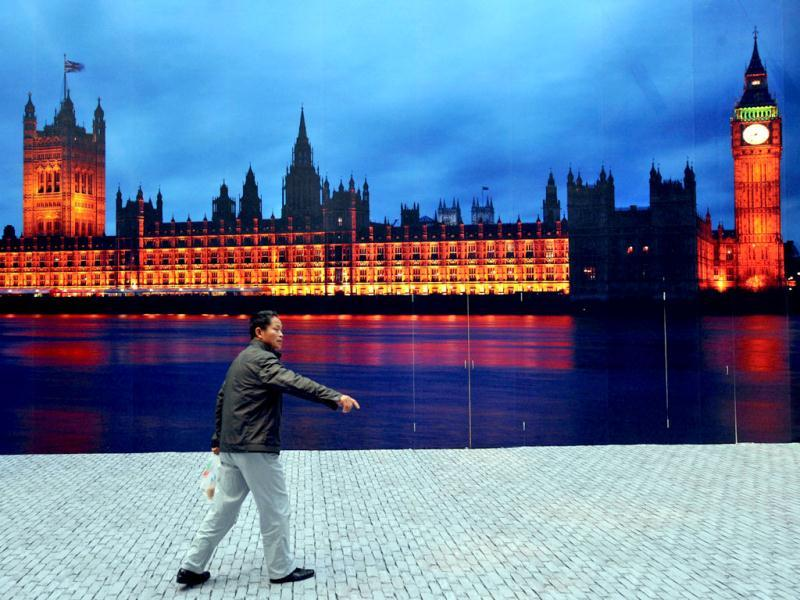 A Chinese man walks by a promotional poster of the London House of Parliament at a ceremony in Beijing to promote the 2012 London Olympic Games. AFP Photo