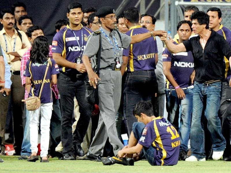 Bollywood actor and IPL franchise Kolkata Knight Riders co-owner Shah Rukh Khan is watched by his daughter Suhana (2L) as he gestures towards a security guard blowing a whistle to direct children accompanying him off the field at The Wankhede Stadium in Mumbai in May, 2012. AFP PHOTO/Indranil MUKHERJEE