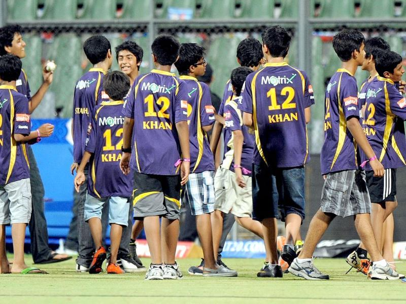 Children accompanying unseen Bollywood actor and Indian Premier League franchise Kolkata Knight Riders co-owner Shah Rukh Khan play in the field after the IPL Twenty20 cricket match between Mumbai Indians and Kolkata Knight Riders at The Wankhede Stadium in Mumbai. AFP PHOTO/Indranil MUKHERJEE