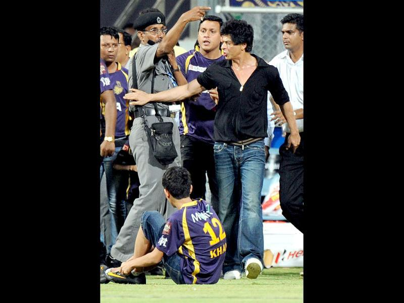 Kolkata Knight Riders co-owner Shah Rukh Khan is accompanied by his daughter Suhana (R) as he gestures towards an unseen security guard after he directed kids accompanying Khan, off the playing field. AFP PHOTO/Indranil MUKHERJEE