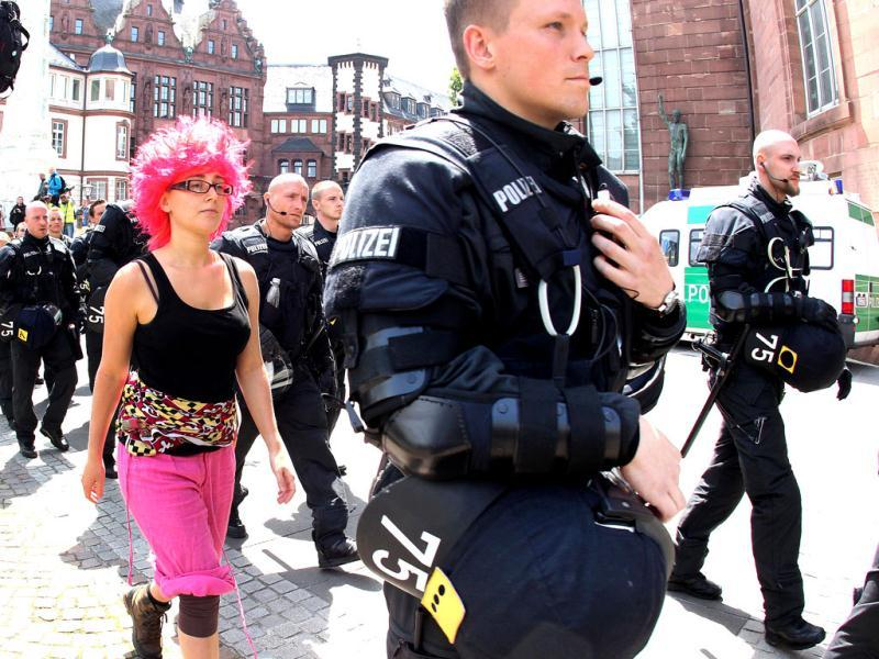 A young woman walks next to police officers during an anti capitalism demonstration in downtown Frankfurt, Germany. AP Photo/Michael Probst