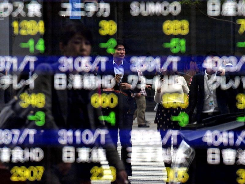 Businessmen reflect on the window of a security company while the stock indicator displaying the stock prices in Tokyo. AFP Photo/Toshifumi Kitamura