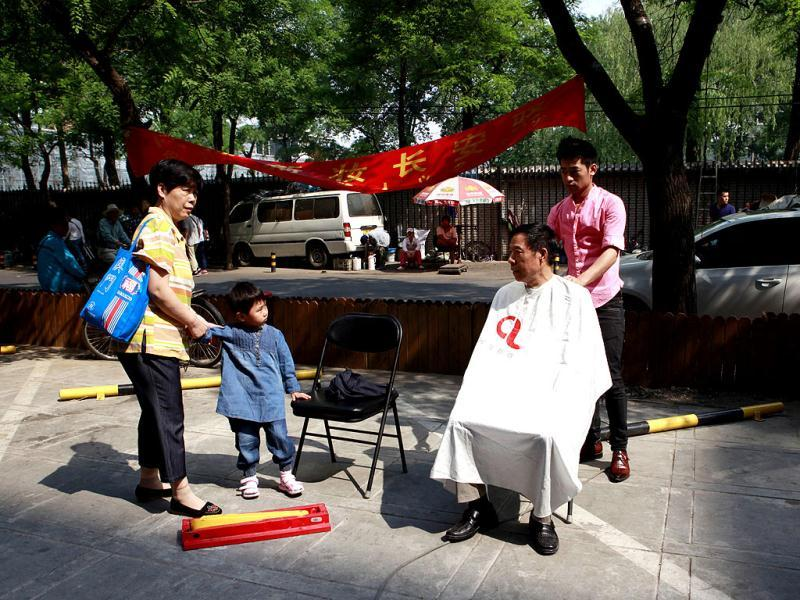 A man gets a free haircut from a barber as part of a community service campaign in Beijing. AP Photo/Ng Han Guan